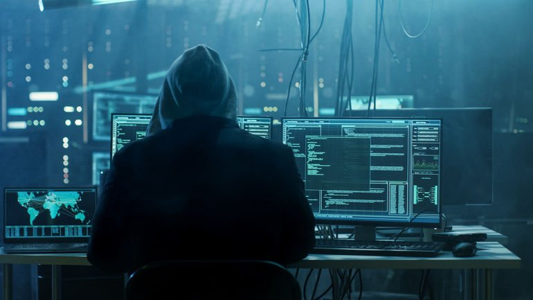 Dangerous_Hooded_Hacker_Breaks_into_Government_Data_Servers_and_Infects_Their_System_with_a_Virus._His_Hideout_Place_has_Dark_Atmosphere,_Multiple_Displays,_Cables_Everywhere.