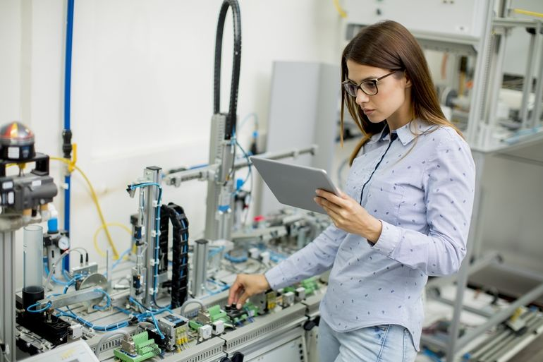 Pretty_young_woman_with_digital_tablet_in_the_electronics_workshop