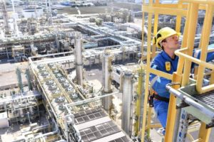chemical_industry_plant_-_workers_in_work_clothes_in_a_refinery_with_pipes_and_machinery_