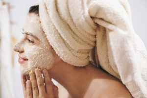 Skin_Care_concept._Young_happy_woman_in_towel_making_facial_massage_with_organic_face_scrub_close_up_in_stylish_bathroom._Girl_applying_scrub_cream,_peeling_and_cleaning_skin.