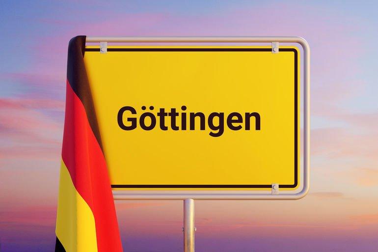 Ortsschild._Flagge_von_Deutschland_hängt_darüber._Himmel_mit_Sonnenuntergang_oder_Sonnenaufgang_
