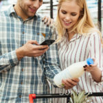 Couple_in_supermarket_reading_shopping_list_on_smartphone