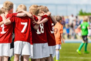 Boys_Soccer_Team._Children_Football_Academy._Kids_Soccer_Players_in_Red_Shirts_Standing_Together_on_the_Pitch._Youth_Soccer_Motivational_Speech._Coach_Motivational_Talk_With_Young_Boys