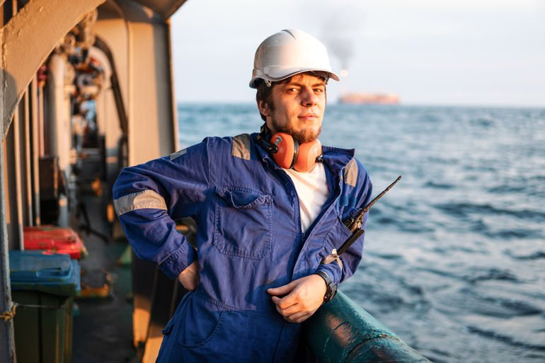 Marine_Deck_Officer_or_Chief_mate_on_deck_of_offshore_vessel_or_ship_,_wearing_PPE_personal_protective_equipment_-_helmet,_coverall._He_has_VHF_walkie-talkie_radio