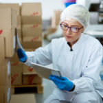 Young_beautiful_focused_female_worker_in_sterile_cloths_using_a_tablet_to_check_correction_of_inventory_in_factory_storage_room.
