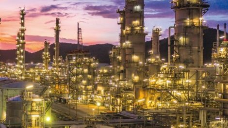 Oil_refinery_with_oil_storage_tank_and_petrochemical_plant_industrial_background_at_twilight,_Aerial_view_oil_and_gas_refinery_at_twilight.