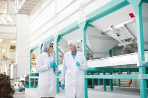 Portrait_of_two_workers_wearing_white_coat_walking_across_clean_production_hall_at_modern_factory,_copy_space