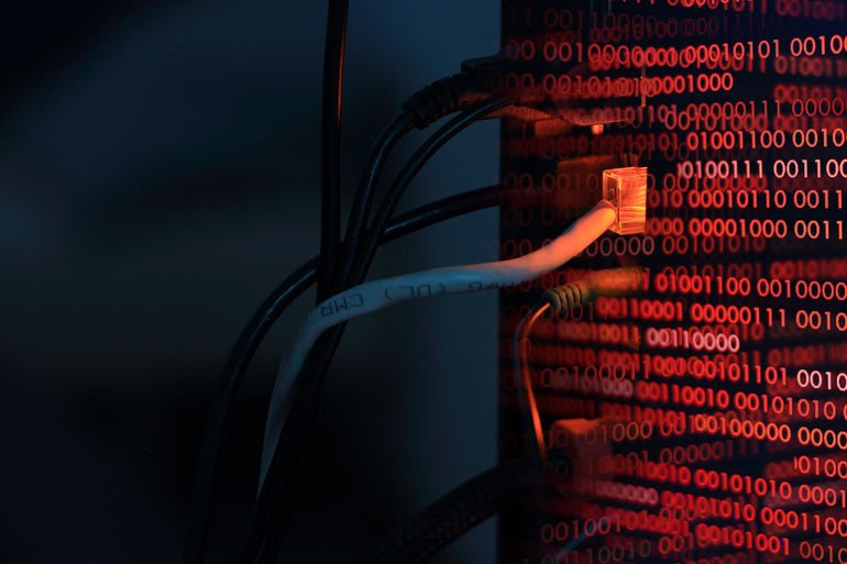 computer_virus_transfer_into_desktop_pc_by_internet_LAN_line._double_exposure_shot_of_backside_of_a_computer_and_red_binary_codes._hacker_virus_spyware_ransomware_and_security_breached_concepts.