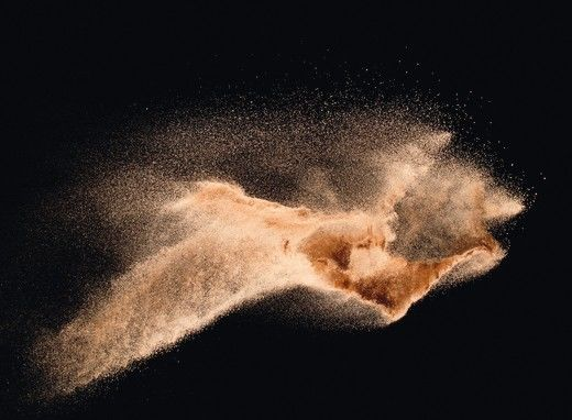 Dry_river_sand_explosion_isolated_on_black_background._Abstract_sand_cloud.Brown_colored_sand_splash_against_dark_background.
