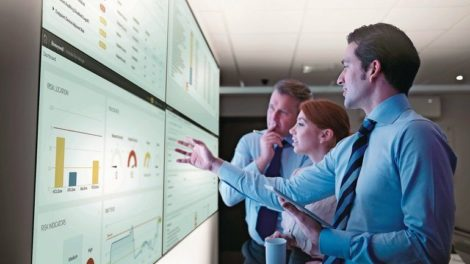 Three_business_people_discuss_graphs_on_screen_in_meeting_room