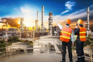 Engineer_survey_of_oil_refiner_and_control_worker_from_portable_radio_on_storage_tank_in_sunset_background