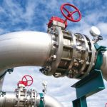 Industrial_zone,_Steel_pipelines_and_valves_against_blue_sky
