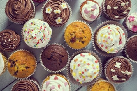 56705074_-_multiple_colorful_nicely_decorated_muffins_on_a_wooden_background,_top_view