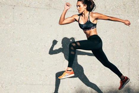 Young_woman_with_fit_body_jumping_and_running_against_grey_background._Female_model_in_sportswear_exercising_outdoors.;_Shutterstock_ID_727673917