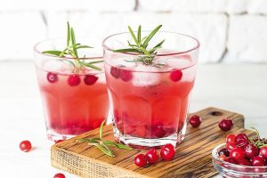 Cocktail_with_cranberry,_vodka,_rosemary_and_ice_on_white.