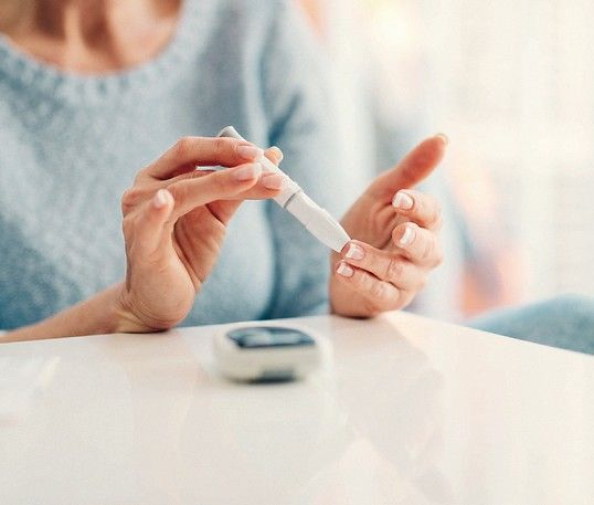 Mature_woman_doing_blood_sugar_test_at_home_in_a_living_room._Selective_focus_to_her_finger._Kraiburg_Thermoplast