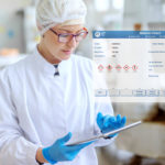 Supervisor_in_sterile_uniform_and_with_eyeglasses_using_tablet_for_controlling_workflow_in_food_factory.